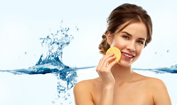 beauty, people and skincare concept - young woman cleaning face with exfoliating sponge over white background and water splash