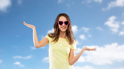 summer, valentine's day and people concept - smiling young woman or teenage girl in heart-shaped sunglasses holding something on palms over blue sky and clouds background