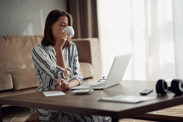 exhausted woman working at home with a laptop and drinking coffee.