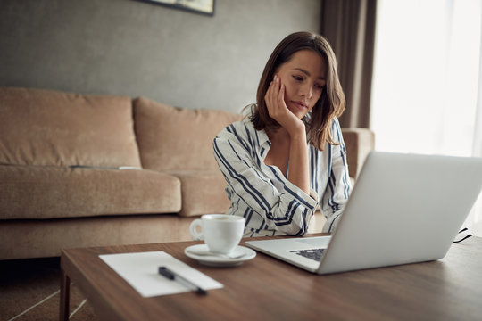 woman works for a computer from a home with a laptop   as a freelancer.