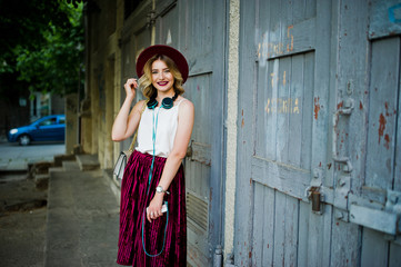 Fashionable and beautiful blonde model girl in stylish red velvet velour skirt, white blouse and hat, posed with phone and earphones.