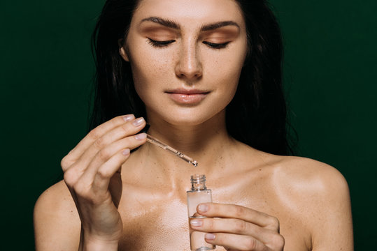 attractive naked woman holding bottle with moisturizing serum isolated on green