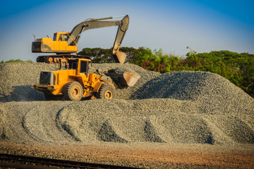 Yellow wheel loader and excavator are working in quarry against the background of crushed stone storage. Wall mural