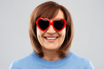 valentine's day, summer and old people concept - portrait of smiling senior woman in red heart-shaped sunglasses over grey background