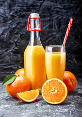 Foto op Canvas Sap Freshly squeezed orange juice in glass bottle with straw. Fruity still life on black backdrop and grey concrete surface rustic style.