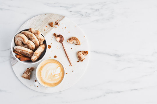 Coffee or cappuccino with latte art and gingerbread biscuits on white marble serving plate over marble background. Breakfast concept. Top view with copy space for text.
