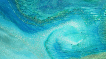 Colorful sparkling paints mix in beautiful patterns. Oil ink of blue, turqoise, green and other colors spread on the surface and mix one into another creating amazing textures and design.