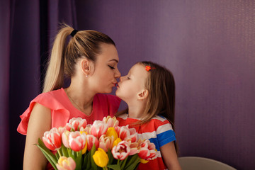 Happy mother's day! daughter congratulates mom and gives a bouquet of flowers to tulips. Happy children and parents, family.