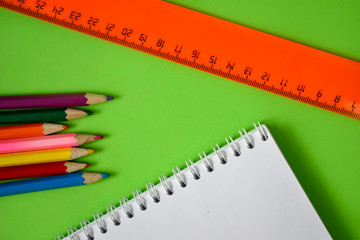 school color pencils and spiral notebook on green background