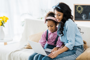 attractive african american woman with adorable daughter using laptop together