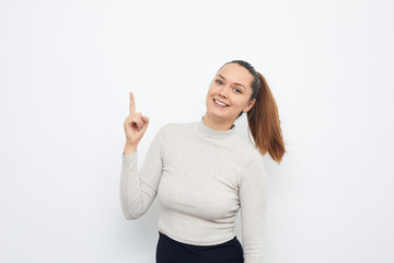 happy young woman pointing up at copyspace
