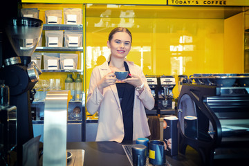 Smiling Coffee shop owner standing behind counter with cup of coffee – Happy woman manager holding cup of coffee proud of her modern cafe business