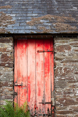 Red and distressed wooden door on an old stone barn with slate tiles