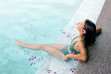Girl relaxing in tropical spa pool with flowers