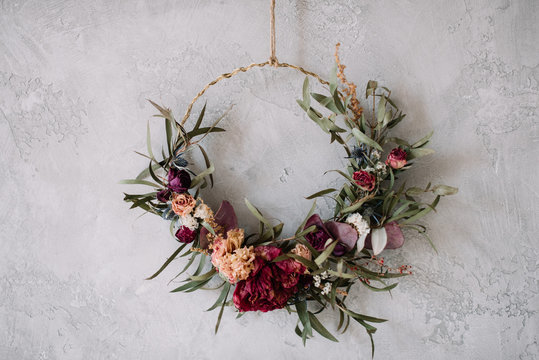 Beautiful hand made everlasting dry wreath made of roses, hydrangea flowers and eucalyptus on the grey wall background