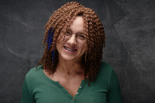 Portrait of a laughing authentic adult woman with afro curls and brequits against a black wall in the studio. Unusual stylish woman with red hair