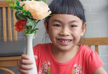 Little girl holding flower vase
