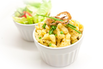 cheese spaetzle with roasted onions and parsley in a white bowl on white plate