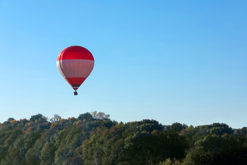 Beautiful view of hot air balloon flying over autumn forest. Space for text