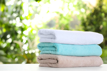 Stack of clean soft towels on table against blurred background. Space for text