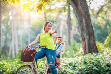 Family on bikes- mother and son riding a bicycle together in park. Wall mural