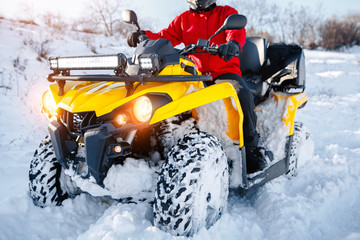 Close up photo of young man in red warm winter clothes and black helmet on the ATV 4wd quad bike stand in heavy snow with deep wheel track. Moto winter sports.