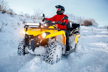 Young man driver in red warm winter clothes and black helmet on the ATV 4wd quad bike stand in heavy snow with deep wheel track. Moto winter sports.