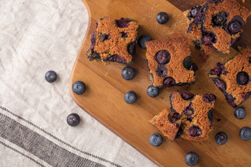 Blueberry square bars on wooden board with blueberries
