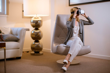 Joyful young woman playing computer games with virtual reality googles at home