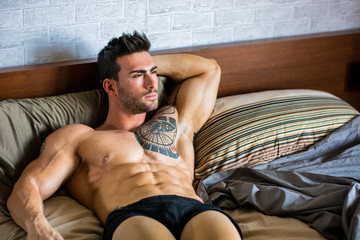 15ca4955c2 Shirtless muscular sexy male model lying alone on bed in his bedroom