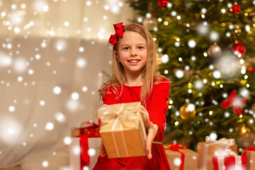 christmas, holidays and childhood concept - smiling girl in red dress with gift box at home