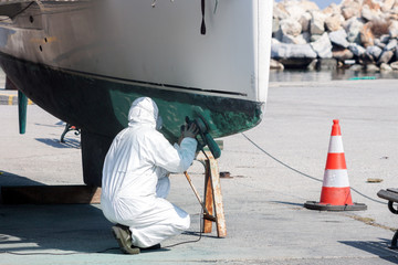 Worker wearing protection suit and mask is sanding down old paint from catamaran