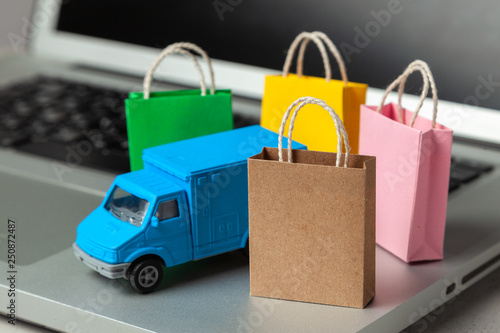 13d006f2 Delivery of orders from the online store. Shopping bags in shopping cart on laptop  keyboard and courier delivery truck