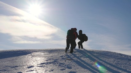 three Alpenists climb rope on snowy mountain. Tourists work together as team shaking heights overcoming difficulties. silhouettes of travelers rise to their victory up hill on ice in rays of sun.