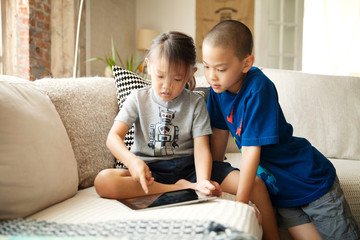 Boy and girl (4-5, 6-7) using tablet pc in living room