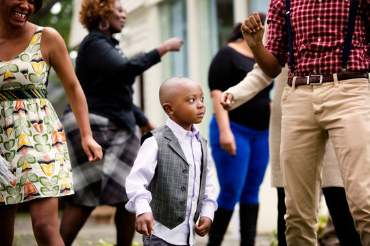 Boy dancing with family members