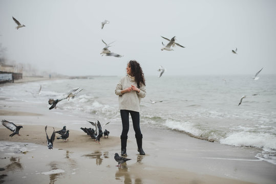 Young curly woman feeding the birds on the sea beach on foggy day