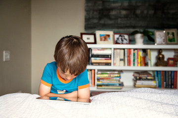 Boy (4-5) on bed with digital tablet