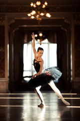 Beautiful ballerina dancing in a hall with a chandelier against the window.