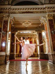 Beautiful ballerina dancing in a arabesque ballet pose against the luxurious interior.