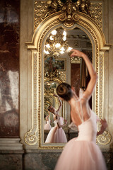 Beautiful ballerina dancing in front of the mirror on background of luxurious interior.