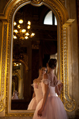 Beautiful ballerina standing in front of the mirror on background of luxurious interior.
