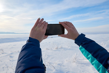 Woman taking a picture of the view with a mobile phone. Field and forest, mountains covered with snow. Blue sky. Frosty clear day.