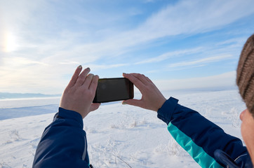 Woman taking a picture of the view with a mobile phone. Field and forest, mountains covered with snow. Blue sky. clear day.