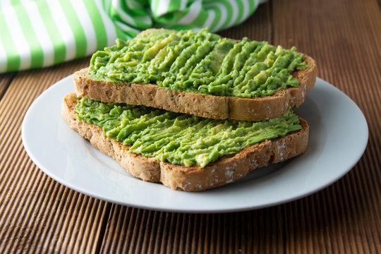 Healthy avocado sandwich, toast bread. Mushed avocado paste, on wooden background. Guacamole.