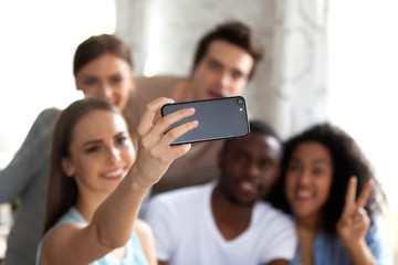 Close up attractive woman holding phone, making selfie with friends