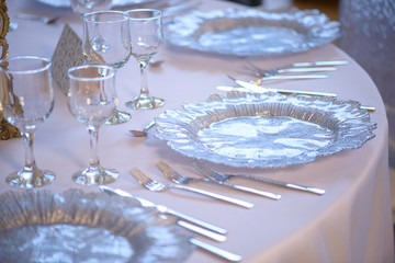 Close-up elegant sitting arrangement at a fine dining restaurant or event featuring transparent plates glassware and silverware in the order of use with white table cloth and chairs with sequin covers