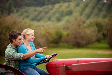 Mid-adult couple driving tractor together