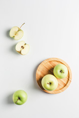 green apples on wooden stand on white background