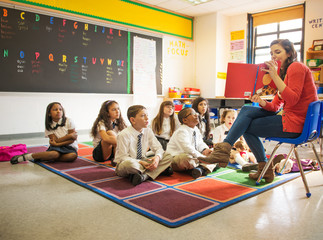 Teacher reading picture book to students (6-7, 8-9, 10-11) in classroom